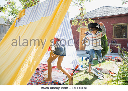 Children playing pirates in backyard fort - Stock Photo