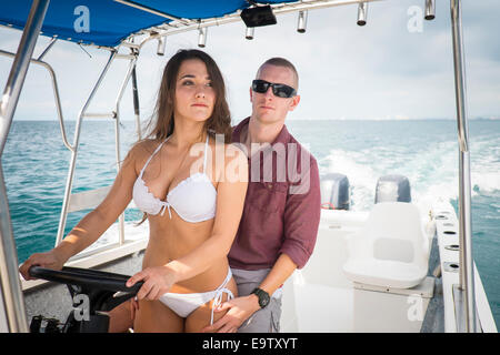 Young woman in bikini and young man riding a boat at sea. She's steering the vessel. - Stock Photo