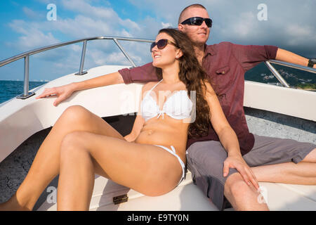 Young woman in bikini sitting next to a man on a fishing boat bow. Both are enjoying the ride on a sunny day. - Stock Photo