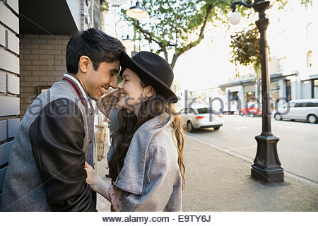 Smiling couple rubbing noses on urban sidewalk - Stock Photo