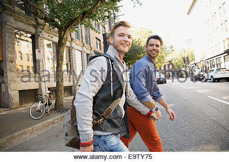 Homosexual couple holding hands and crossing urban street - Stock Photo