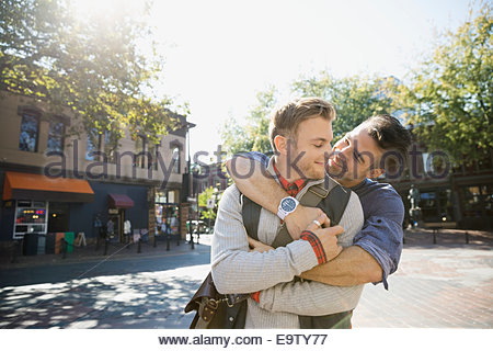 Homosexual couple hugging on sunny urban street - Stock Photo