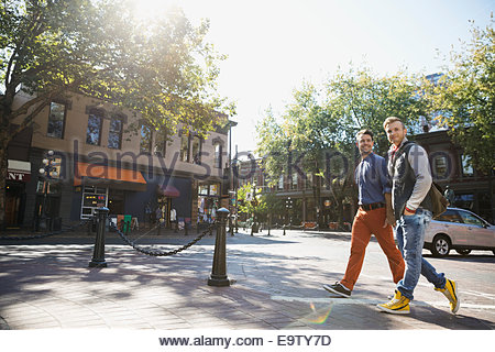 Homosexual couple walking on sunny urban street - Stock Photo