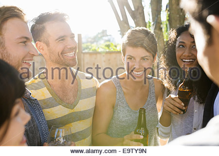 Friends drinking and hanging out at backyard barbecue - Stock Photo