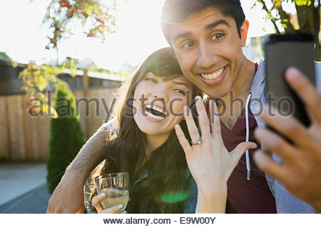 Enthusiastic couple taking selfie of engagement ring - Stock Photo