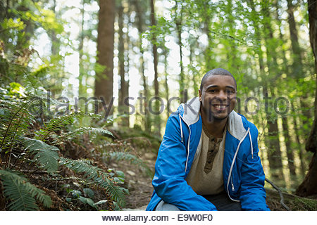 Portrait of young man smiling in woods - Stock Photo