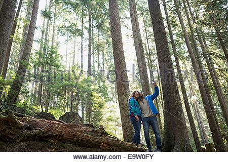 Young couple taking selfie below trees in woods - Stock Photo