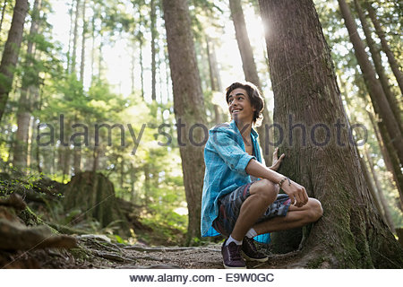 Teenage boy crouching by tree in woods - Stock Photo