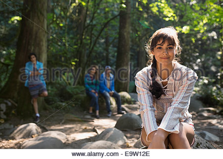 Portrait of smiling young woman in woods - Stock Photo