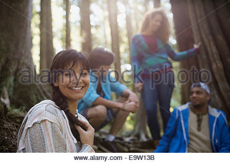 Portrait of smiling woman with friends in woods - Stock Photo