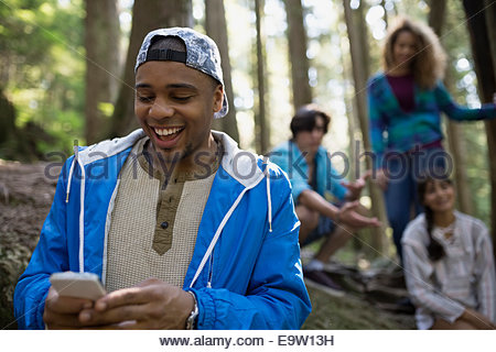 Enthusiastic young man using cell phone in woods - Stock Photo