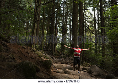 Exuberant man with arms outstretched in woods - Stock Photo