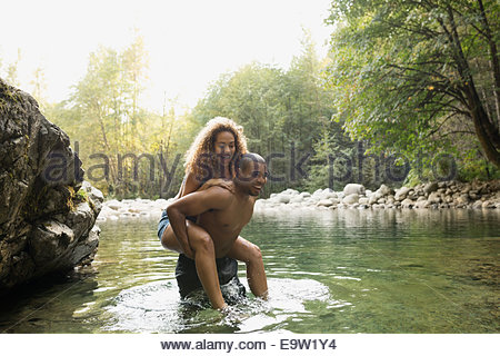 Couple piggybacking at swimming hole in woods - Stock Photo