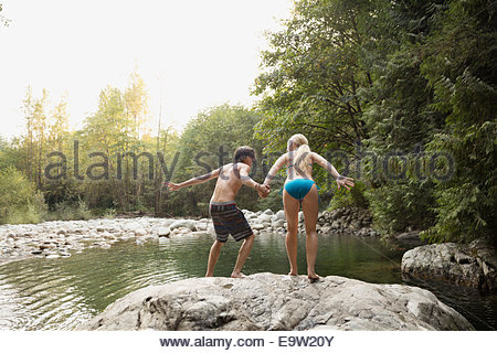 Couple holding hands and jumping from rock - Stock Photo