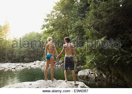Couple holding hands on rock at swimming hole - Stock Photo