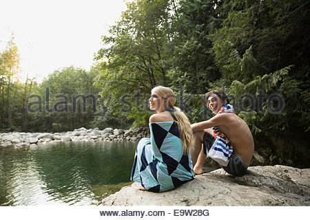 Couple wrapped in towel at swimming hole - Stock Photo