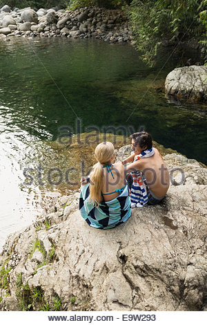 Couple relaxing on rock at swimming hole - Stock Photo