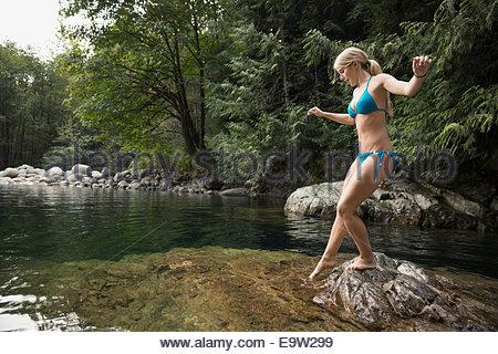Young woman in bikini dipping toe in water - Stock Photo