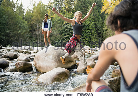 Friends jumping rocks over creek in woods - Stock Photo