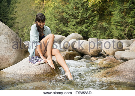 Woman dipping feet in creek in woods - Stock Photo