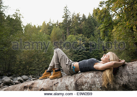 Young woman laying on fallen tree in woods - Stock Photo