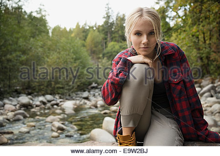 Portrait of serious woman at creekside in woods - Stock Photo