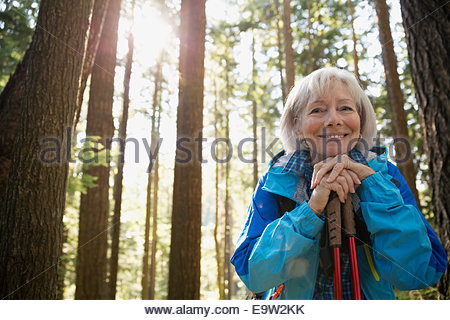 Portrait of smiling senior woman hiking in woods - Stock Photo