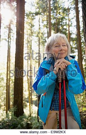 Serene senior woman hiking in sunny woods - Stock Photo