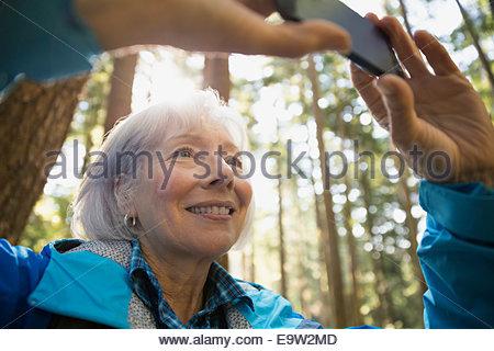 Senior woman using camera phone in woods - Stock Photo