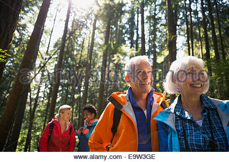 Senior couple hiking in sunny woods - Stock Photo