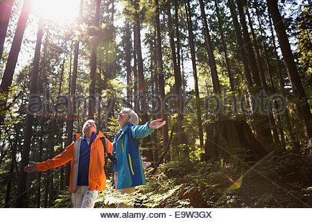 Senior couple with arms outstretched in sunny woods - Stock Photo