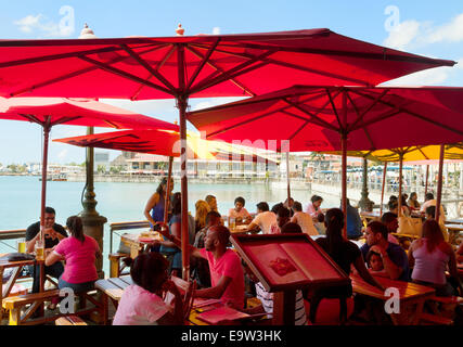People sitting at a cafe in the  Caudan Waterfront, Port Louis, Mauritius - Stock Photo