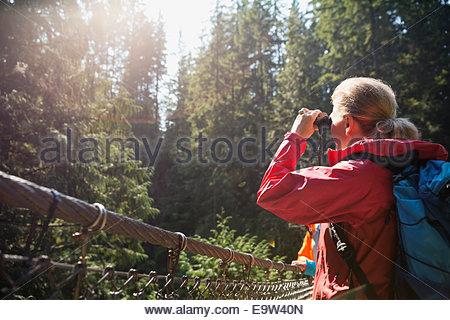 Woman using binoculars in sunny woods - Stock Photo