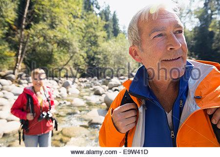 Senior man hiking in sunny woods - Stock Photo