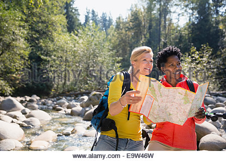 Women looking at trail map in sunny woods - Stock Photo
