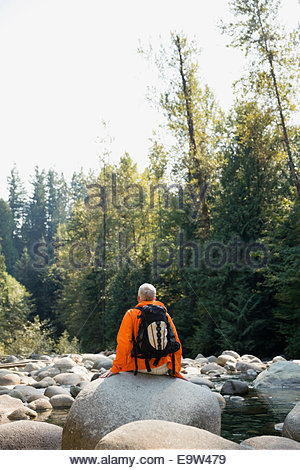 Man with backpack on rock at creek - Stock Photo