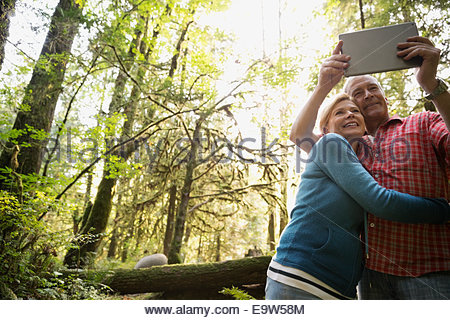 Couple taking selfie with digital tablet in woods - Stock Photo