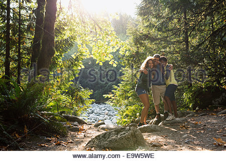 Portrait of friends hugging in sunny woods - Stock Photo
