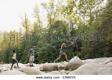 Friends crossing rocks over creek in woods - Stock Photo