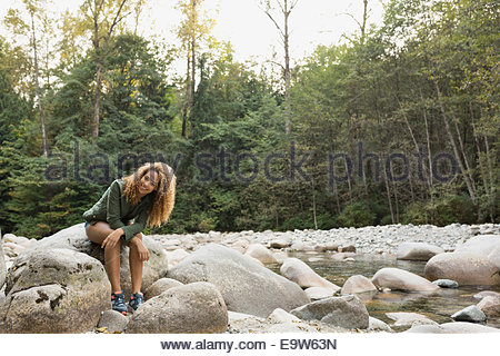Portrait of smiling woman on rock at creekside - Stock Photo
