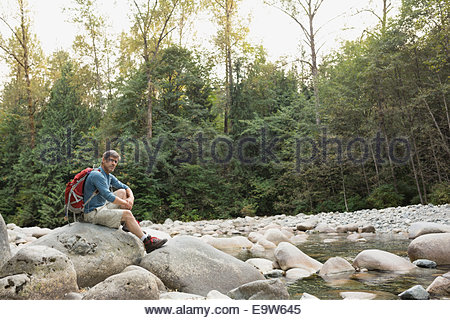 Man with backpack sitting on rocks at creekside - Stock Photo