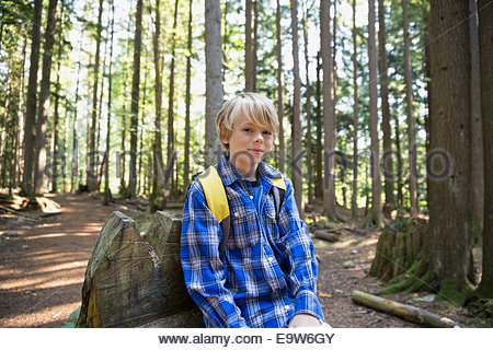 Portrait of boy with backpack in woods - Stock Photo
