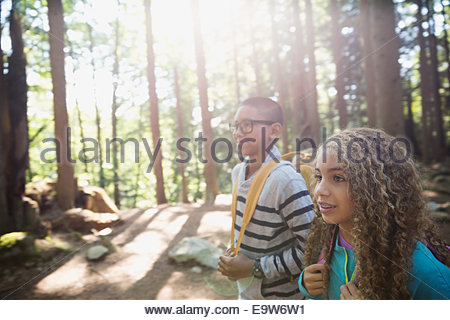Boy and girl hiking in sunny woods - Stock Photo