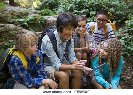 Teacher and children using digital tablet in woods - Stock Photo