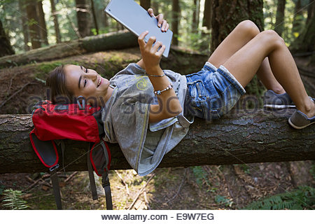 Girl with digital tablet laying on fallen tree - Stock Photo