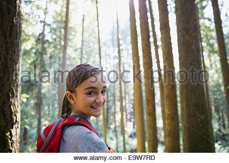 Portrait of smiling girl in woods - Stock Photo