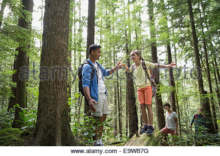 Father helping daughter balance on fallen tree - Stock Photo
