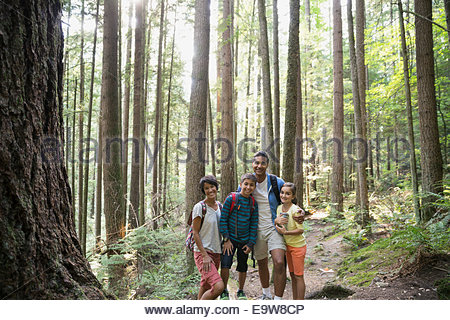 Portrait of smiling family hugging in woods - Stock Photo