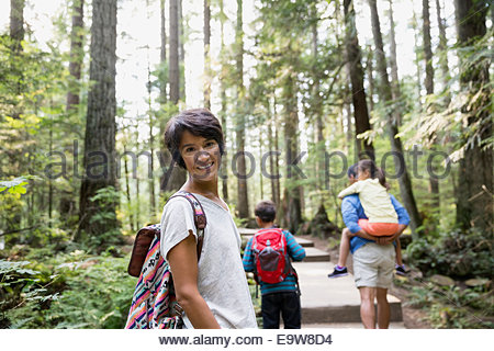 Portrait of smiling woman with family in woods - Stock Photo