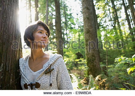 Serene woman leaning against tree in woods - Stock Photo